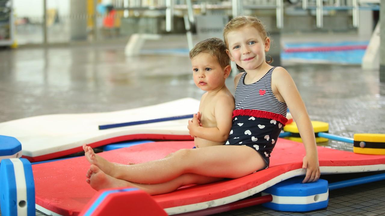 Zwei kleine Kinder auf der Schwimmmatte im blu, © Kathleen Friedrich