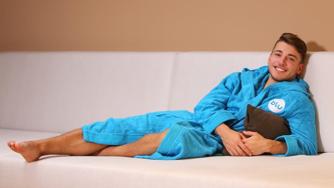 Junger Mann im azurblauen Bademantel liegt auf der Couch im blu sauna, © Kathleen Friedrich