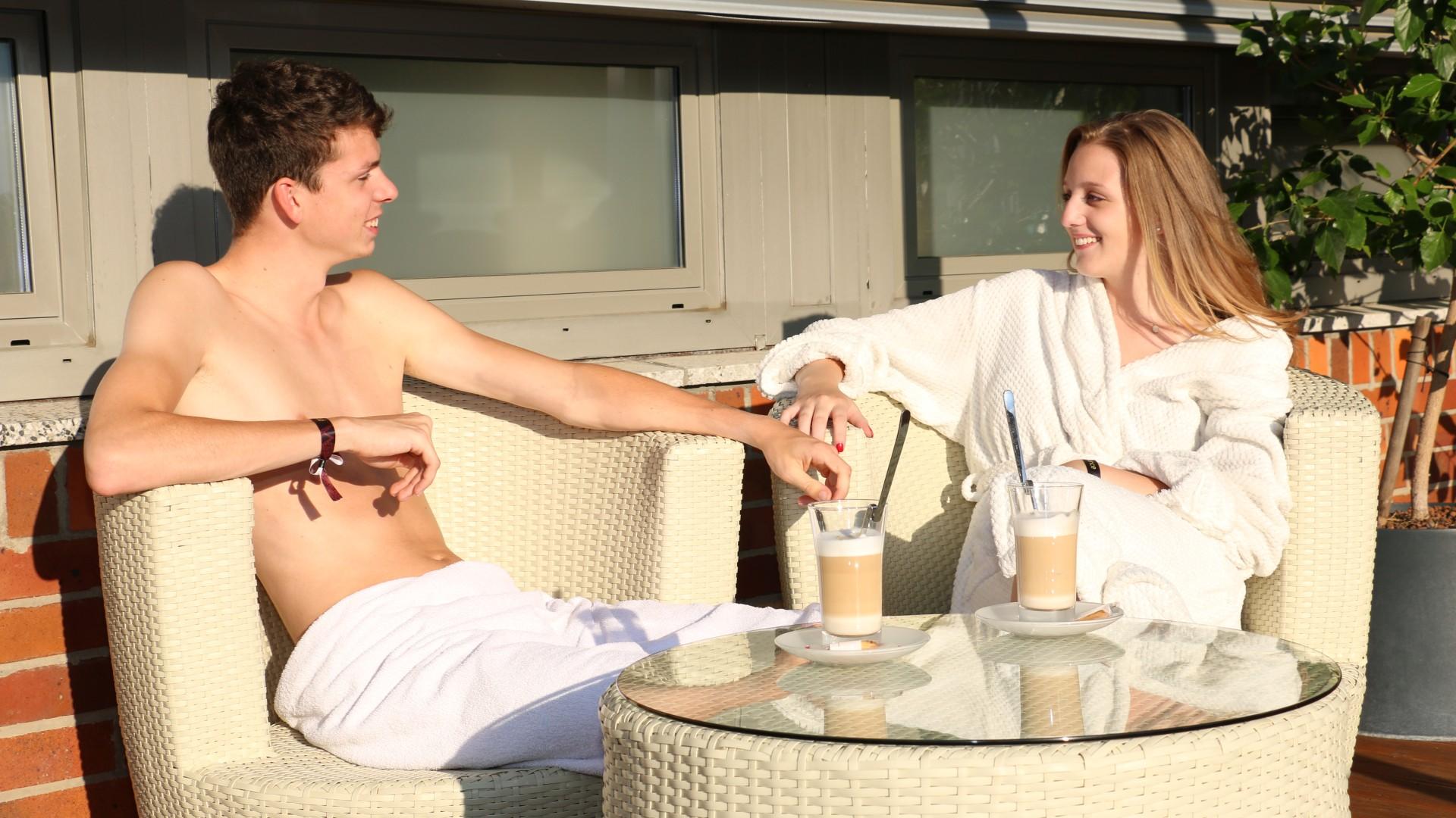 Junges Paar sitzt auf der Dachterasse und trinkt  Kaffee, © Jan Seelig