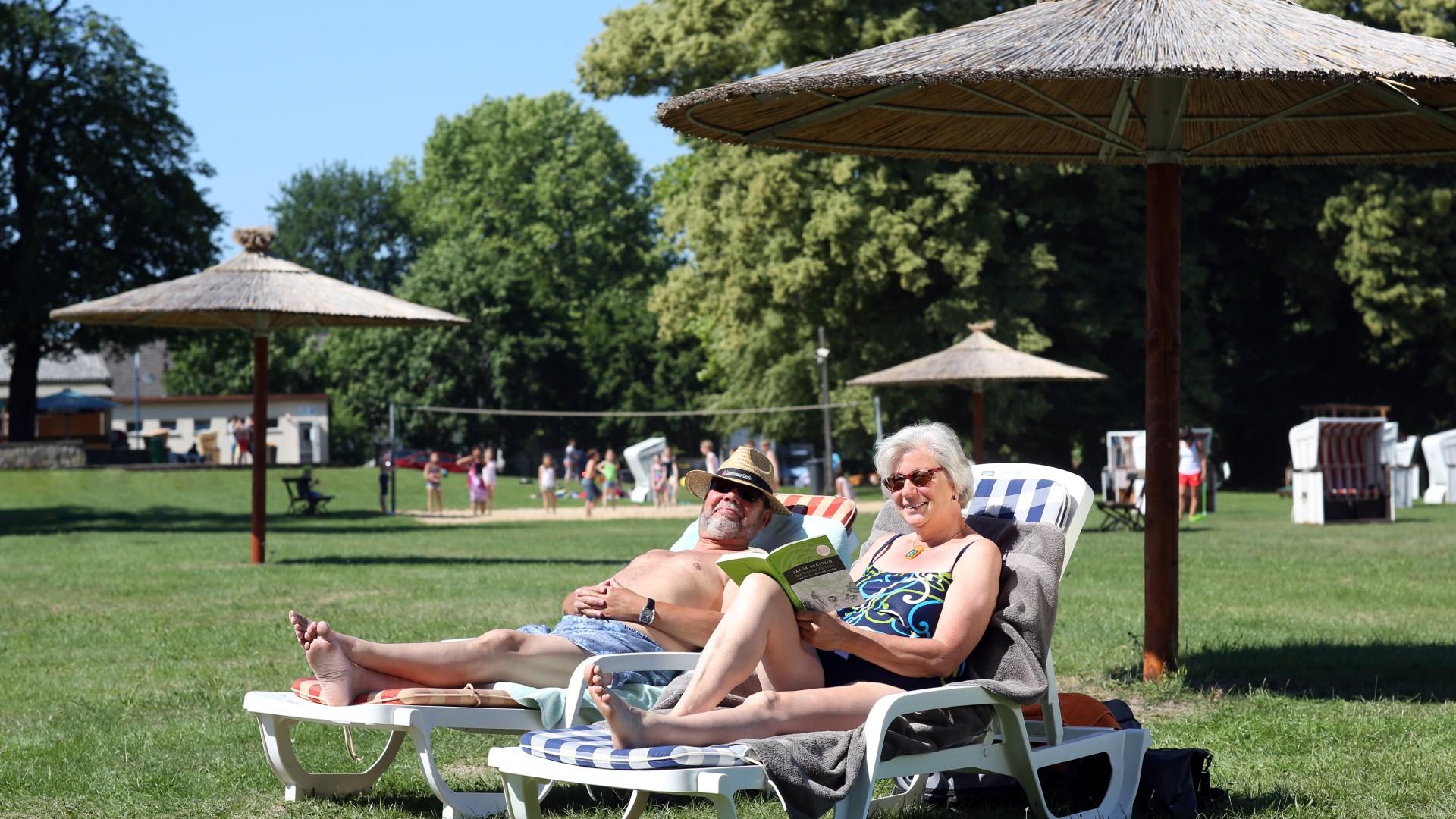 Älteres Ehepaar entspannt im Strandbad Park Babelsberg unter den großen Sonnenschirmen aus Stroh, © Kathleen Friedrich