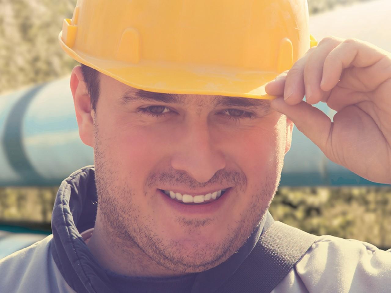 Bauarbeiter mit gelben Helm vor der Fernwärmeleitung