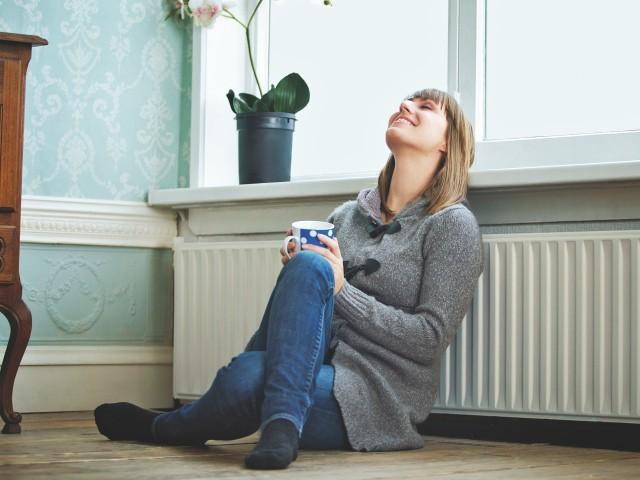 Junge Frau lehnt sich mit dem Rücken an warmer Heizung an, © m-imagephotography /iStock
