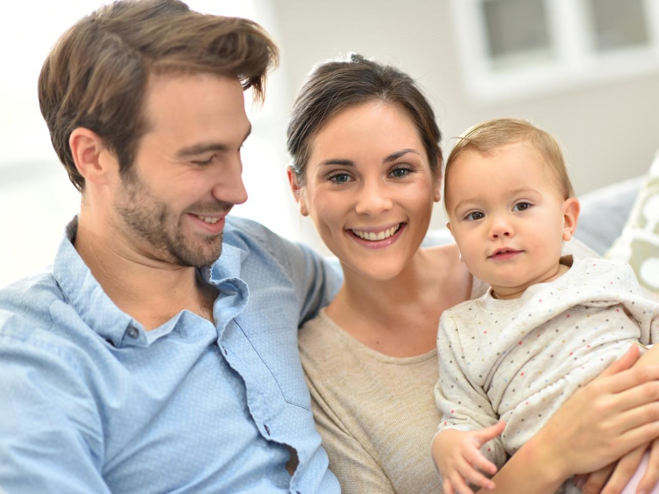 Portrait einer glücklichen jungen Familie im Wohnzimmer, © goodluz – stock.adobe.com