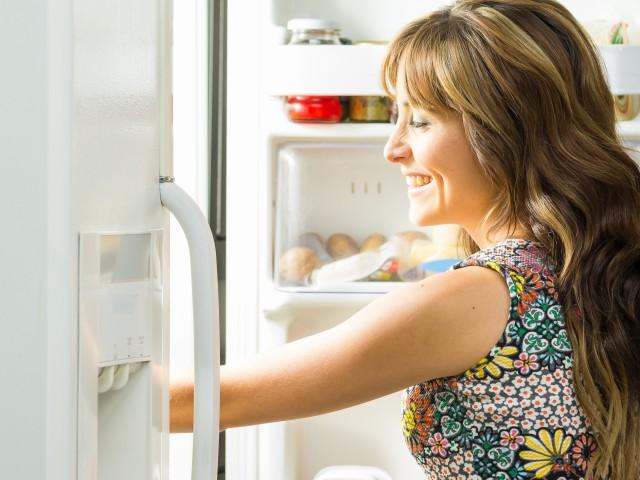 Lächelnde Frau öffnet Kühlschrank, © Fotos 593 /Fotolia