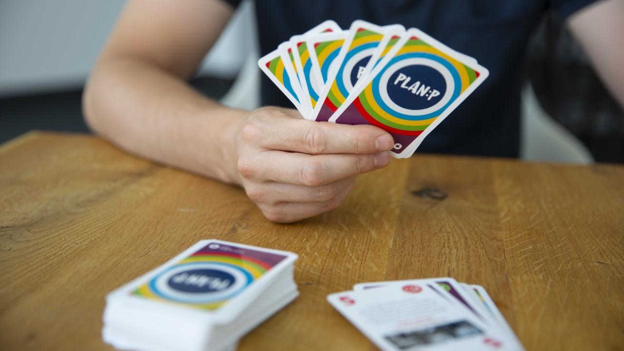 Mann spielt Kartenspiel Plan:P am Tisch