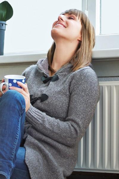 Frau mit Rücken an der Heizung genießt Wärme