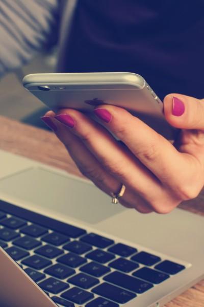 Frau sitzt am Schreibtisch vor dem Laptop und hält ihr Smartphone in der Hand