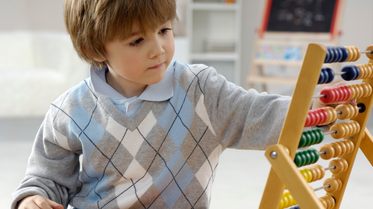 Kind mit Rechenschieber zählt Strom- und Gasrechnung nach, © acilo /iStock