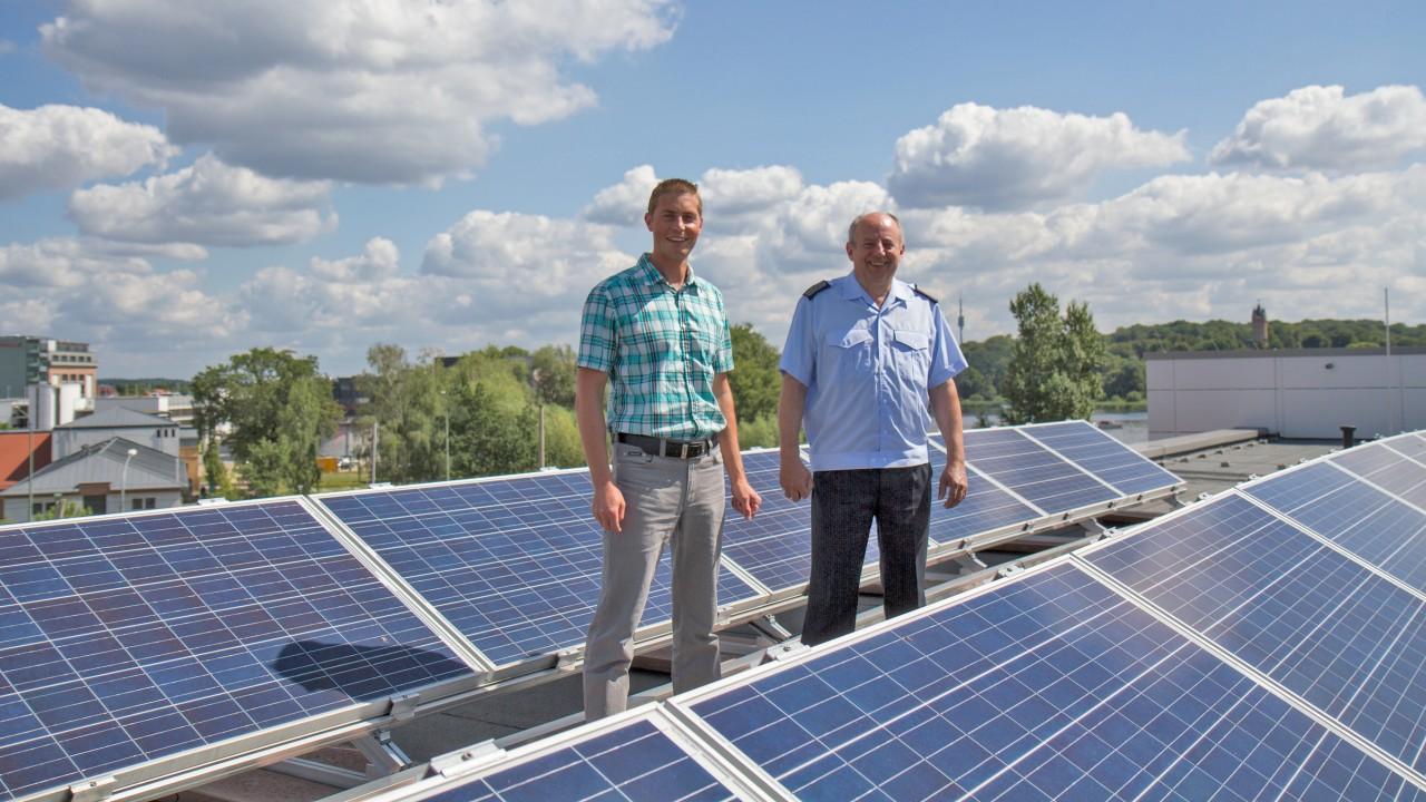 Mitarbeiter der Energie und Wasser Potsdam uhd der Feuerwache bei der Photovoltaik-Anlage auf dem dach der Feuerwache in Potsdam