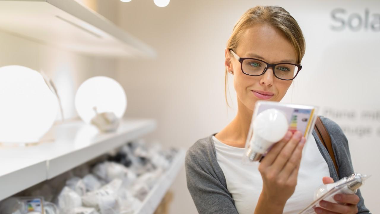 Frau beachtet beim Einkauf von LED-Lampen die Energieeffizienzklassen, © lightpoet /Fotolia