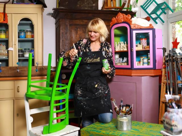 Frau streicht Stuhl grün an in Atelier, © Beate Wätzel