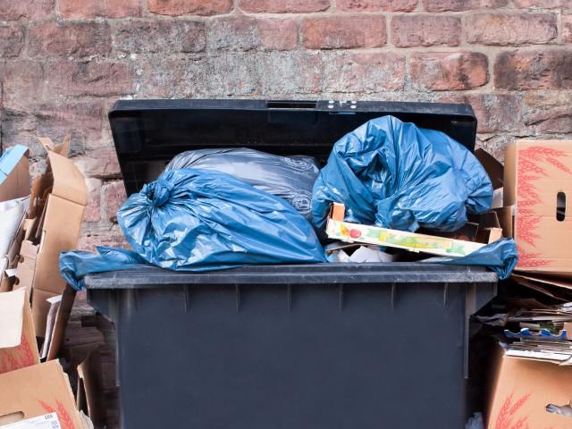 Schwarzer Müllgroßbehälter gefüllt mit blauen Abfallsäcken und gestapalete Kartons stehen vor einer Steinwand, © eyetronic /Fotolia