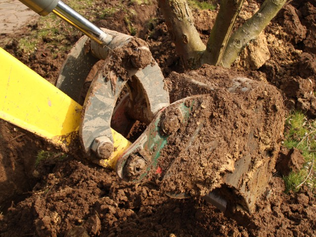 Baggerschaufel hebt Erde aus dem Boden bei Gartenarbeiten, © Riko Best /Fotolia
