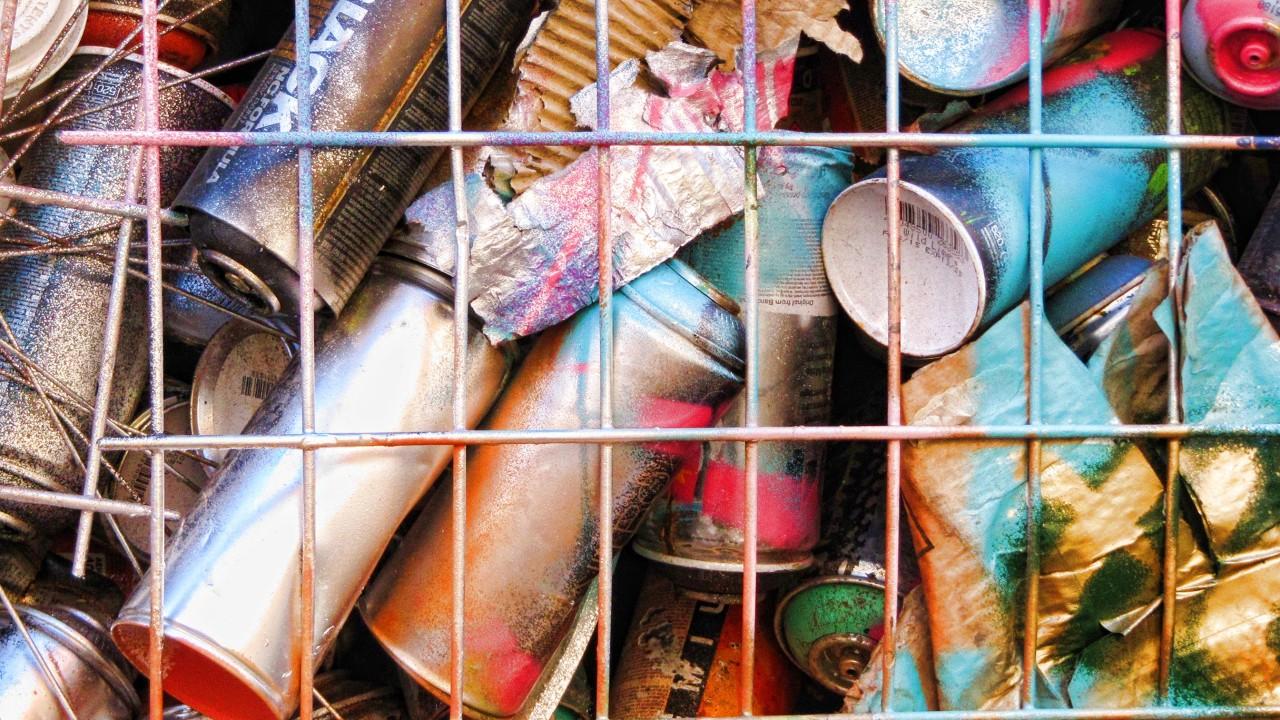 Gitterbox auf dem Schadstoffhof voller alter Spray- und Farbdosen