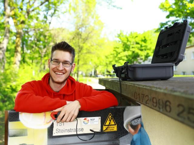 Junger Student der Industriellen Elektrotechnik mit rotem Hoodie steht an einer Trafostation, © Katheeln Friedrich