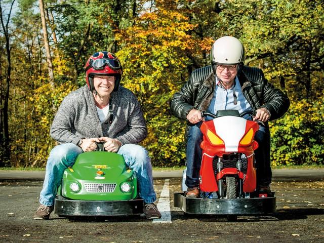 Cover unseres Kundenmagazins: 2 Herren fahren um die Wette auf einem Elektro-Bobbycar und einem Mini-Elektro-Motorrad