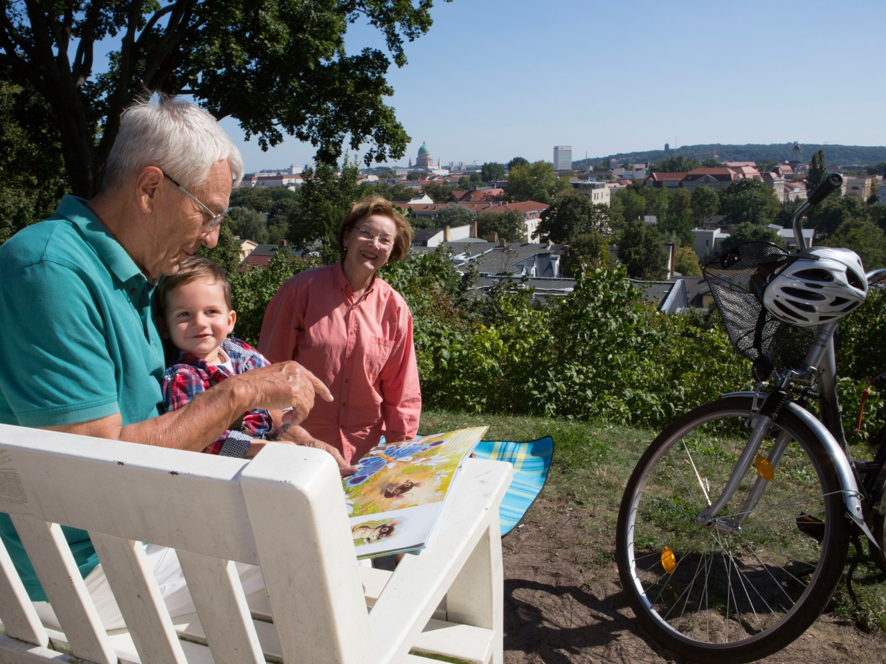 Großeltern mit dem Enkel sitzen auf einer weißen Bank mit dem Blick auf Potsdam, © Kathleen Friedrich