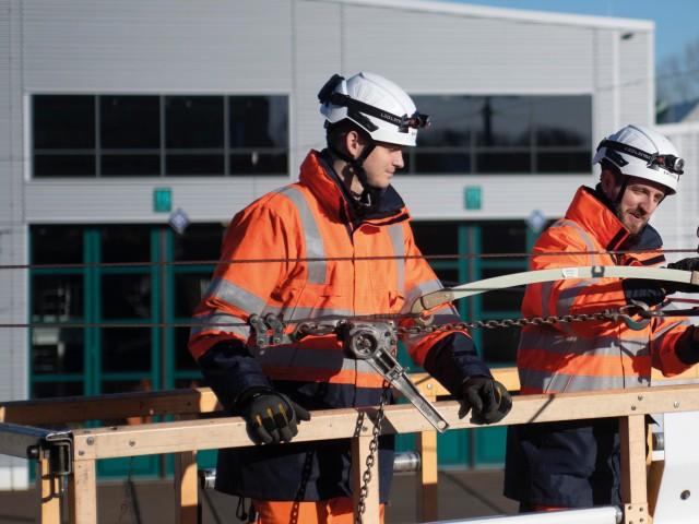 Mitarbeiter im Bereich Infrastruktur bei der Arbeit an Fahrleitungsmasten