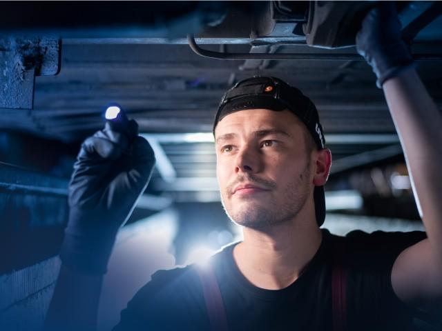 Mitarbeiter aus dem Bereich Werkstatt unter einer Straßenbahn mit Taschenlampe, © vip/kontur