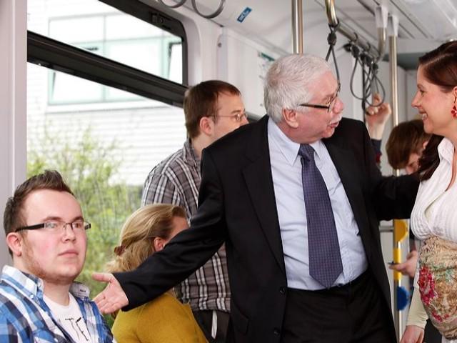 Fahrgast bietet einer schwageren Frau einen Platz in der Bahn an.