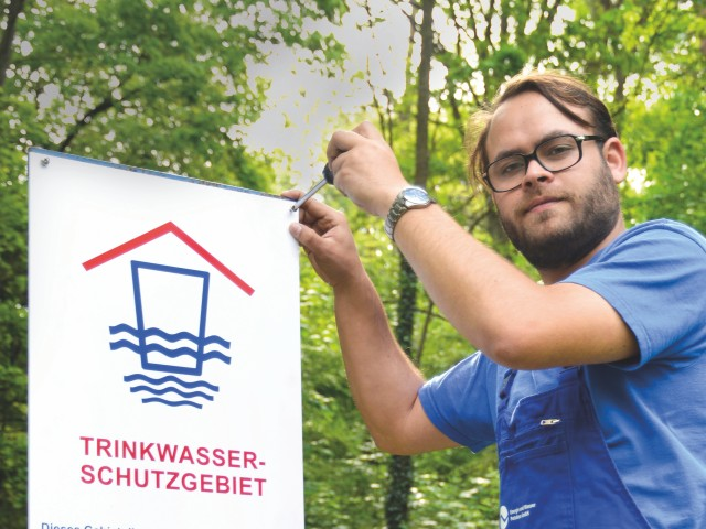 Mitarbeiter der Energie und Wasser Potsdam montiert ein Trinkwasserschutzgebiet-Schild vor einem Brunnen, © Sabeth Stickforth