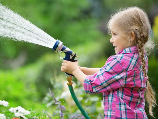 Mädchen mit Gartenschlauch spritzt Wasser im Garten