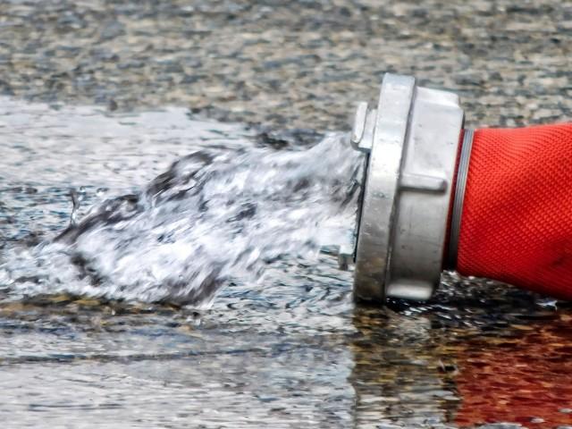 Löschwasser läuft am Ende eines roten Feuerwehrschlauches auf die Straße
