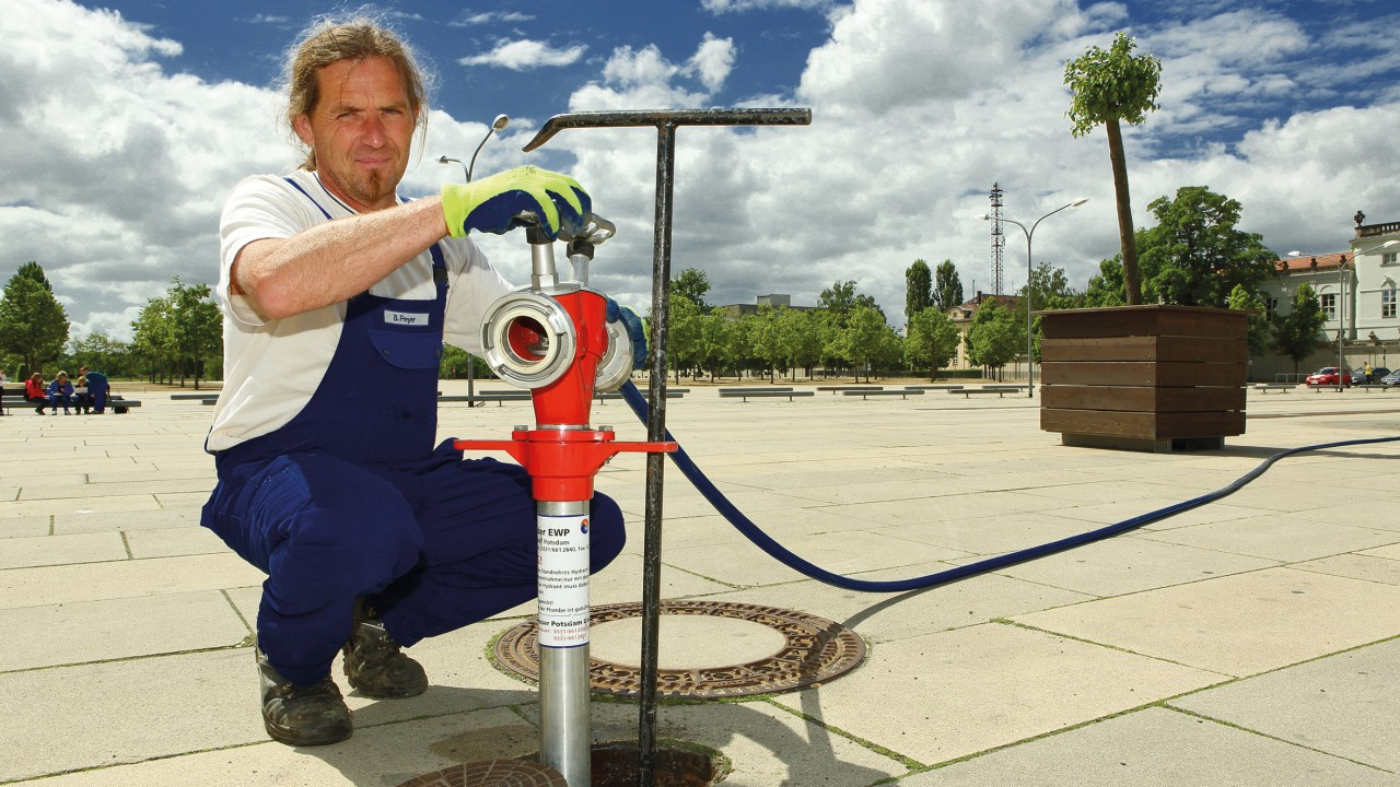 Mitarbeiter der Energie und Wasser Potsdam schließt ein Standrohr für ein Fest am Hydranten an, © Beate Wätzel
